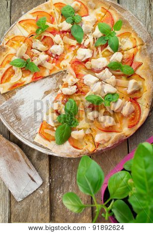 Rustic pizza topped with fresh basil leaves