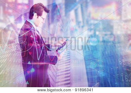 Businessman standing while using a tablet pc against low angle view of skyscrapers