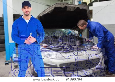 Smiling male mechanic holding spanner against mechanic examining car engine