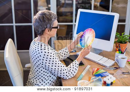 Casual businesswoman looking at colour chart in the office