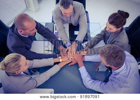 Business team putting their hands together in the office