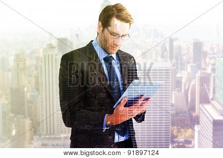 Businessman using a tablet computer against city skyline