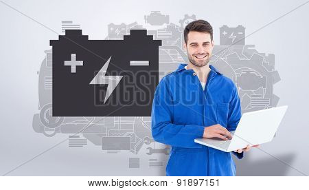 Happy young male mechanic using laptop against grey vignette