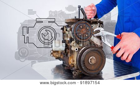 Male mechanic repairing car engine against grey vignette