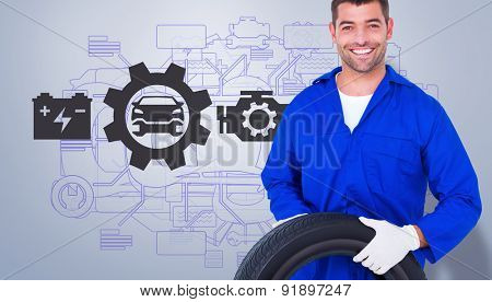 Mechanic holding tire on white background against grey vignette
