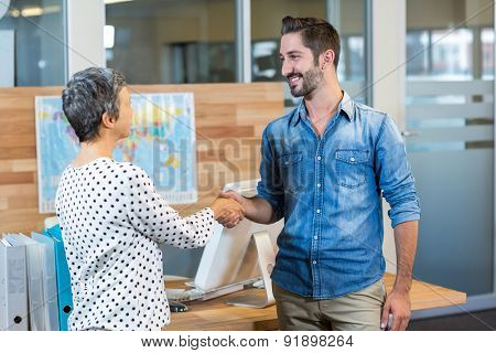 Smiling business people shaking hands in the office