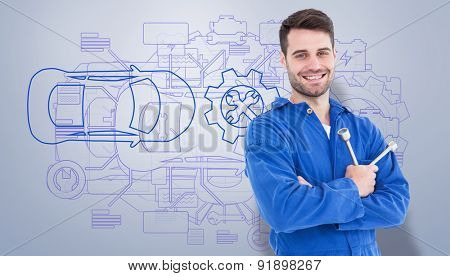 Smiling young male mechanic holding spanner against grey vignette