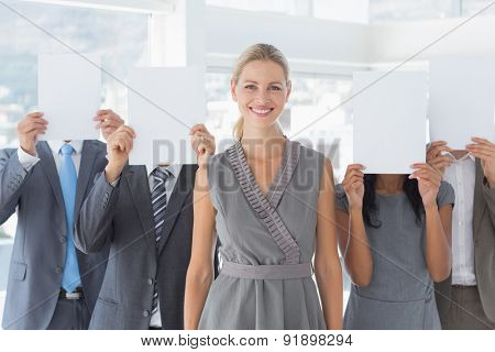 Business colleagues hiding their face with paper in the office