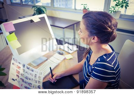 Happy editor working at her desk in creative office