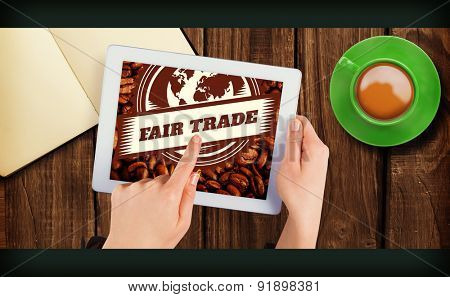 Fair Trade against hands holding tablet