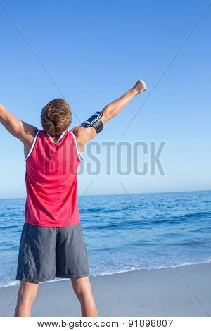 Handsome man raising arms at the beach