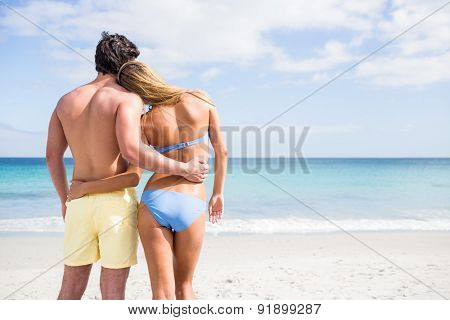 Happy couple embracing and looking at the sea at the beach