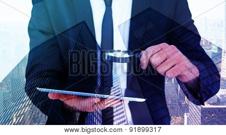 Businessman looking at his tablet through magnifying glass against skyscraper