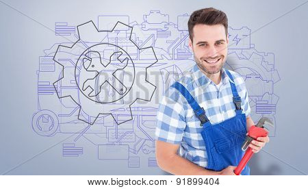 Confident young male repairman holding monkey wrench against grey vignette