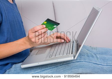 Woman doing online shopping with laptop and credit card on the couch