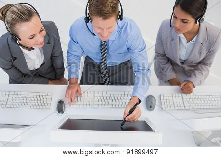 Businessman showing his screen to the team in call center