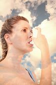 pic of inhalant  - Woman using inhaler for asthma against blue sky with white clouds - JPG