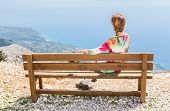 stock photo of sitting a bench  - Woman sitting on brown wooden bench on top of mountain looking at panorama of coast with sea in Greece - JPG