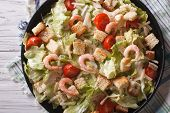 image of caesar salad  - Delicious Caesar salad with shrimps closeup on a black plate - JPG