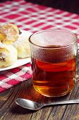 stock photo of baked raisin cookies  - Cup of hot tea and cookies wit raisins on rustic table - JPG