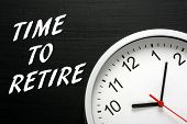 picture of last day work  - The phrase Time To Retire in white text on a blackboard next to a modern wall clock - JPG