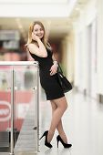 picture of black heel  - Smiling attractive young woman holding suede handbag wearing black color clothes - JPG