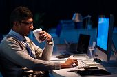 stock photo of programmers  - Programmer drinking coffee and computing at night side view - JPG