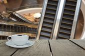 pic of escalator  - Defocus with terrace wood and cappuccino coffee with escalators in shopping mall for background usage - JPG