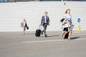stock photo of carry-on luggage  - Businesspeople with luggage running on street - JPG