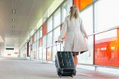 picture of carry-on luggage  - Full length rear view of young businesswoman with luggage rushing in railroad station - JPG