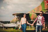image of girl walking away  - fun and stylish couple walking near the aircraft and looks away - JPG