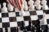 stock photo of chessboard  - Hand with white pawn over chessboard closeup - JPG