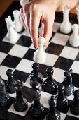 pic of chessboard  - Hand with white pawn over chessboard closeup - JPG