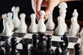 image of chessboard  - Hand with white pawn over chessboard closeup - JPG