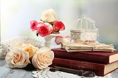 pic of vintage antique book  - Fresh roses with old book and letters on color wooden table - JPG