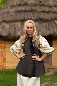 pic of national costume  - Young woman in ukrainian national costume near old historic house - JPG