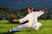 image of tai-chi  - tai chi exercise in nature on green field slovenia europe - JPG