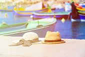 foto of maltese  - two hats with traditional maltese boats on background - JPG