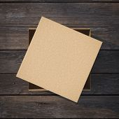 stock photo of fedex  - Cardboard box with a cap on the wooden table - JPG