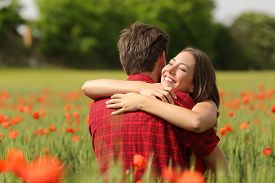 stock photo of hug  - Happy couple hugging affectionate after proposal in a green field with red flowers - JPG