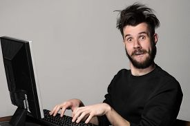 pic of crazy face  - Funny and crazy man using a computer on gray background - JPG
