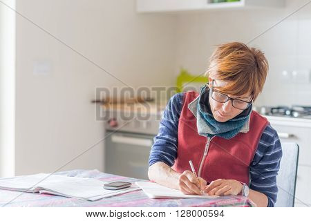 Woman with eyeglasses sitting at table reading and handwriting paperwork and documents. Selective focus home interiors. Concept of working at home.