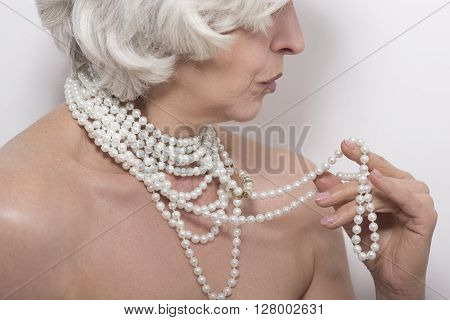 Closeup portrait of mature naked woman demonstrating her expensive beads in studio over white background. Naked concept.