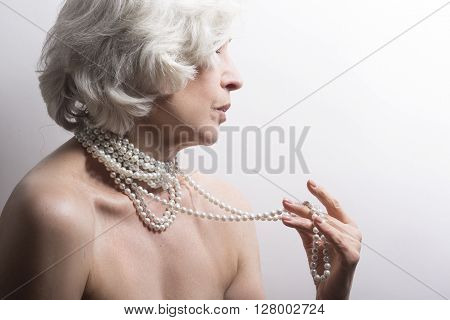 Naked concept. Mature naked woman showing ner beautiful beads over white background in studio. Blond senior woman.