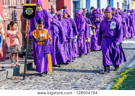 Antigua Guatemala - March 24 2016: Local men & boys dressed as penitents take part in Holy Thursday procession in colonial town with most famous Holy Week celebrations in Latin America.