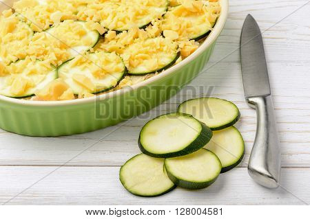 Casserole with zucchini, chickent and cheese before cooking.