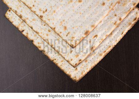Matzo three on brown table closeup photo