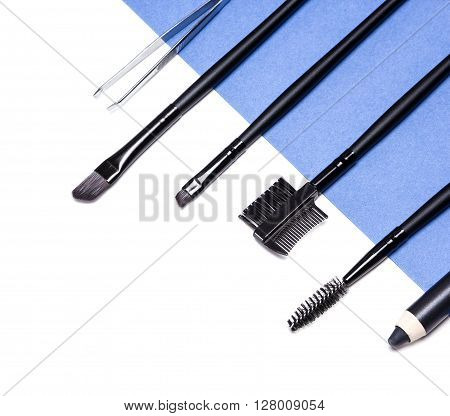Close-up of accessories for care of the brows: eyebrow pencil, angle brushes, spooly brush, tweezers and brow comb / brush combo on white and blue background. Eyebrow grooming tools