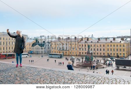 HELSINKI, FINLAND - APRIL 23, 2016: The girl take pictures of herself with view of the Senate Square from the Helsinki Cathedral. In the center is Czar Alexander II Statue by Finnish sculptors Walter Runeberg and Johannes Takanen