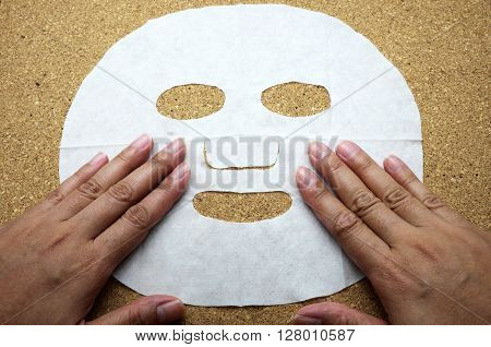 Facial mask with woman hands on cork message board/bulletin board.
